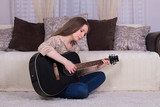 Young beautiful woman playing black guitar sitting on carpet at home.