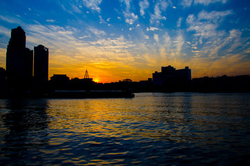 Sunset on the city center downtown river waterfront with tall building backdrop, hotel, resort, building, apartment