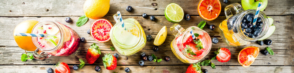 Selection various fruit and berry lemonade drinks, refreshment infused water, in mason jars, with fresh strawberry, lemon, lime, oranges, blueberry,  copy space © ricka_kinamoto