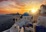 Romantischer Sonnenuntergang über dem malerischem Dorf Oia auf der Insel Santorini, Kykladen, Griechenland
