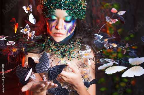 Foto Murales natural nymph with horns like branches of a tree and butterflies circling around. Fantasy style costume