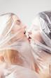 Plastic kiss. Closeup portrait of two beautiful woman in polyethylene wrap