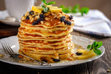 Pancakes with honey, nuts and raisins with a cup of coffee