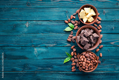 obraz lub plakat Chocolate, cocoa and cocoa beans on a blue wooden background. Top view. Free copy space.