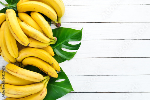 Banana with green leaves on a white wooden table. Tropical Fruits. Top view. Free copy space. - 248209656