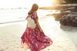 Beautiful girl in boho maxi dress on the beach