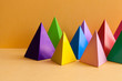 Minimal geometric still life background. Three-dimensional pyramid prism rectangular on orange background. Colorful yellow blue pink green violet red colored objects.
