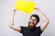Portrait of a smiling young bearded man dressed in black shirt holding empty speech bubble over white.background