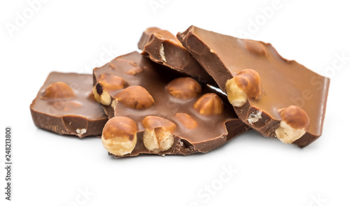 fototapeta na ścianę Pieces of chocolate with whole nuts on white.