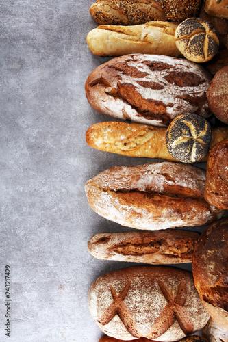 Leinwandbild Motiv Assortment of baked bread and bread rolls on stone table background