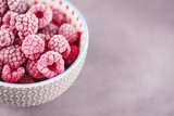 Frozen raspberries in a gray bowl on a gray background. Copy space