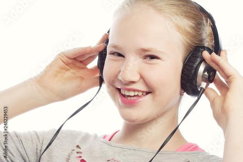 Beautiful happy little girl with headphones