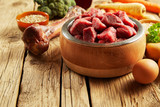 Pet food in a wooden bowl with fresh meat