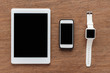 Top view of digital tablet, smartphone and smartwatch with blank screen on wooden background