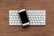 Top view of keyboard and smartphone with blank screen on wooden background