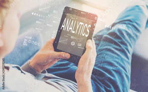 Leinwandbild Motiv Analytics with man using a tablet in a chair