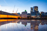 london bridge and skyscrapers reflecting at night