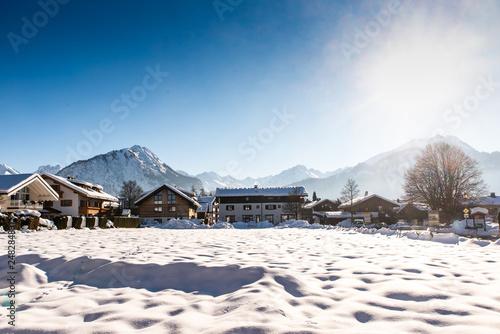 Leinwandbild Motiv Winter in Oberstdorf mit Schnee und Alpen im Gegenlicht