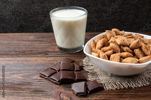 Dried breakfast pads in white bowl, milk and chocolate bar on dark wooden background. © Natallia