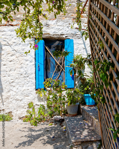 Greece, blue window shutters on traditional Mykonos house white washed stone wall