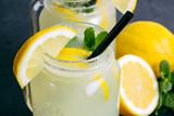 Refreshing lemonade drink with lemon slice and mint in the jar on dark background