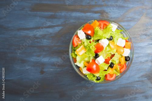 Foto Murales Greek salad in glass bowl on black or dark gray wooden or metal table