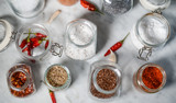 Various spices in glass jars on a white marble table flat lay - 248316271