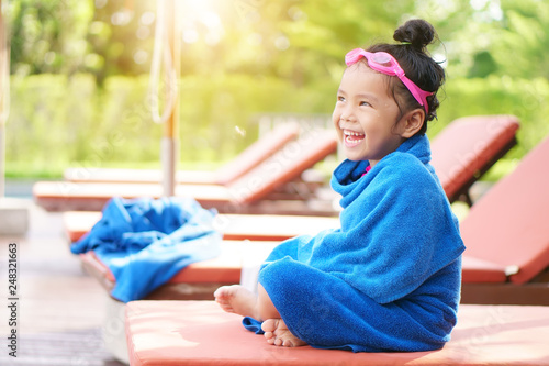 Leinwanddruck Bild Asian child or kid girl laugh smiling with wet cold and sit on bed or pool chair with blanket towel on swimming pool with happy in water park for refreshing relax or exercise on summer holiday travel