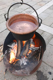 fire lit to boil water inside the large copper cauldron during h