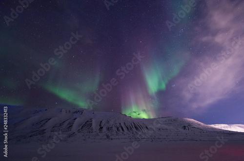 Leinwanddruck Bild The polar arctic Northern lights aurora borealis sky star in Norway travel Svalbard in Longyearbyen city the moon mountains