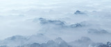 Aerial of rough steep snowy mountains in fog. - 248333234