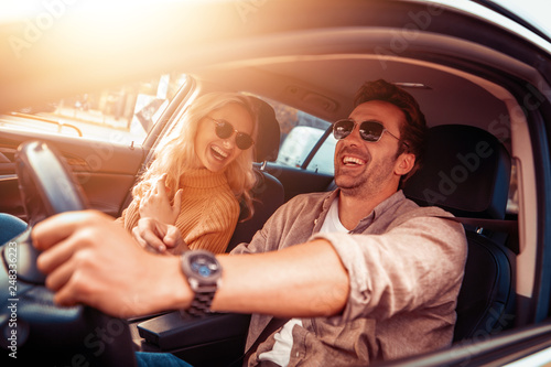 Foto Murales Happy couple in car on road trip smiling at each other