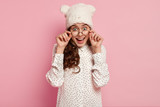 Photo of pleasant looking cheerful young woman with appealing appearance, tender smile, holds both hands on frame of spectacles, wears hat and polka dot shirt, isolated over pink background.