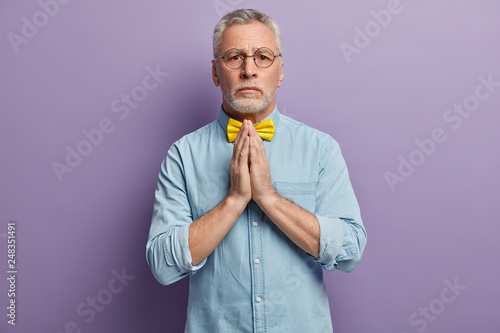 People, age and spirituality concept. Serious mature wrinkled man keeps hands pressed together, believes in good luck, wears denim elegant shirt and yellow bowtie, isolated over purple background