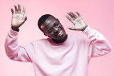 Young handsome african american man dancing, singing his favorite song with closed eyes, isolated on pink background