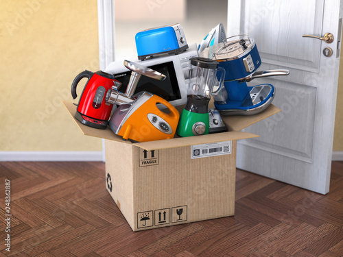 Leinwanddruck Bild Home  kitchen appliances in open cardboard box. Delivery,  e-commerce and online shopping concept. Microwave oven, blander,  processor, toaster, teapot.