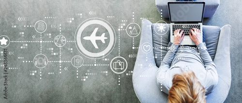 Leinwanddruck Bild Airplane travel theme with man using a laptop in a modern gray chair