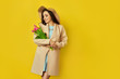 Fashion photo of a beautiful young woman with tulips in her hand .she dressed in a beautiful coat,  and T-shirt with stripes on the yellow background .Spring concept. March 8. beautiful girl.
