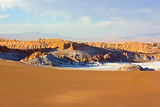 Unearthly landscape of sand and rock formations of Atacama Desert, Chile, South America. Sunset over vastness of the desert spreading towards mountain ridge on horizon. - 248404406
