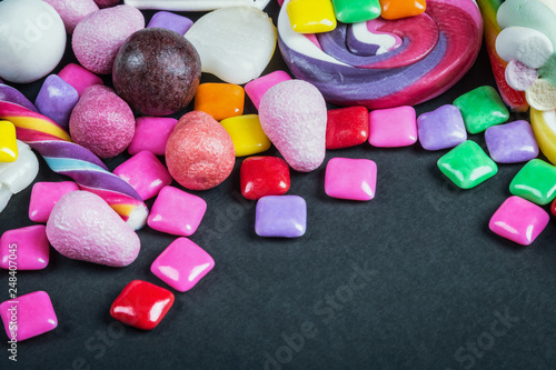 chewing gum, candy, chewing candy and other sweets on black background - 248407045