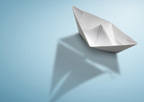 maritime travel concept, paper ship with sailing boat shadow - 248420261