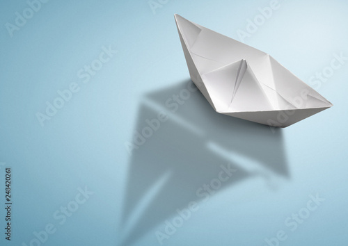 maritime travel concept, paper ship with sailing boat shadow