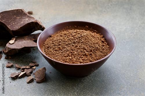 Leinwanddruck Bild Organic carob powder in a bowl. Natural cocoa substitute. Close up view