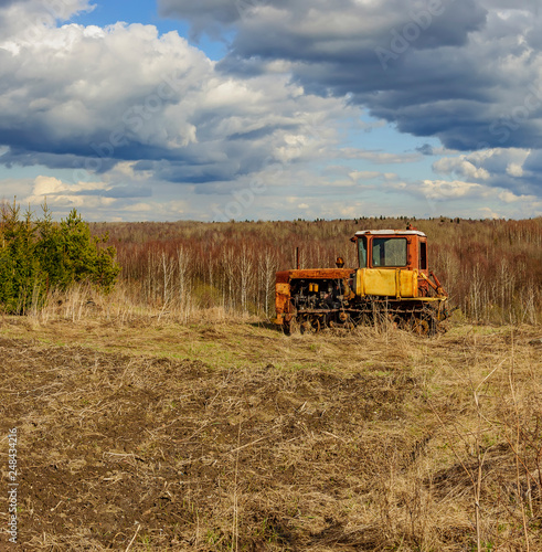 Foto Murales Cloudy day in early spring. Abandoned broken-down tractor. Russia. Leningrad region.