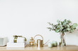 Leinwandbild Motiv Modern interior design concept. Minimal Nordic Scandinavian style living room with wooden table with gift box, floral bouquet with eucalyptus, candles, radio at white wall. Pastel apartment for rent.