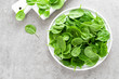 Leinwanddruck Bild - Fresh spinach leaves on white plate. Healthy vegan food. Top view