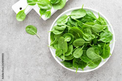 Leinwanddruck Bild Fresh spinach leaves on white plate. Healthy vegan food. Top view