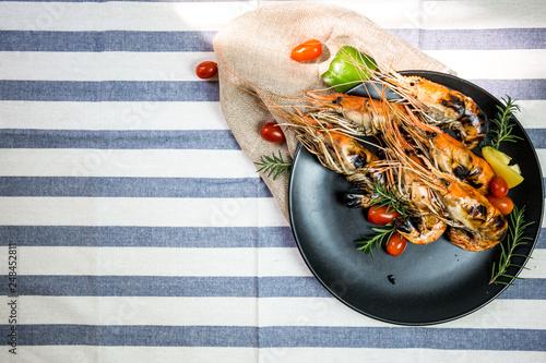 Grilled orange shrimp on a black plate - 248452811