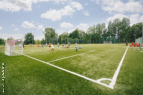 Leinwanddruck Bild Blurred picture of soccer field at school on summer day time. Background image of blurred football pitch. Image for background usage