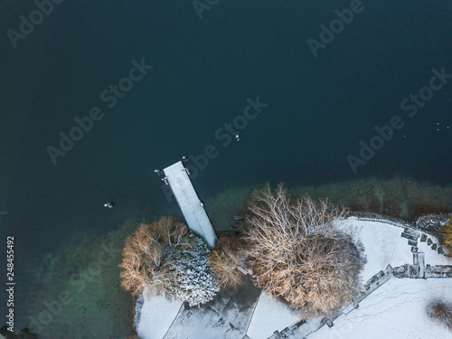 Aerial view of snow covered landing stage on lake. Trees in winter time on cold morning with snow on branches. © Mario